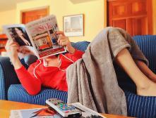 девушка на диване читает газету